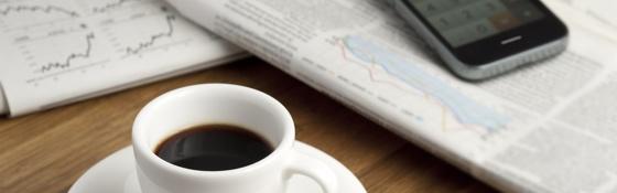 Krant met kop koffie en iPhone