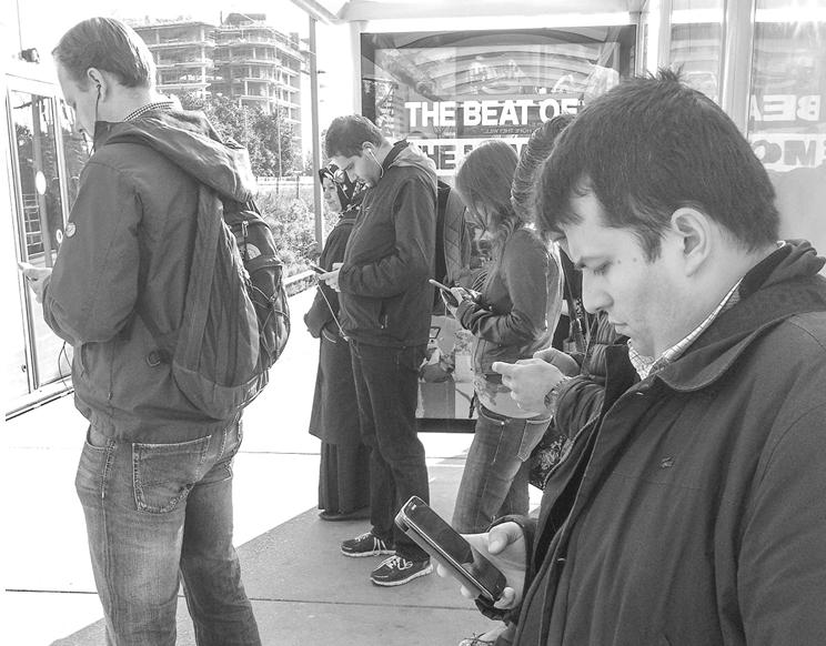 Mensen bij bushalte kijken op smartphone