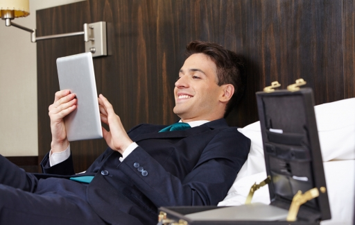 Successful business man working with tablet PC in his hotel room (c) Robert Kneschke/Shutterstock