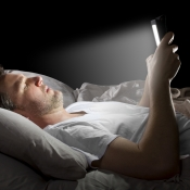 Man in bed met scherm, via Shutterstock (shutterstock_192354611).