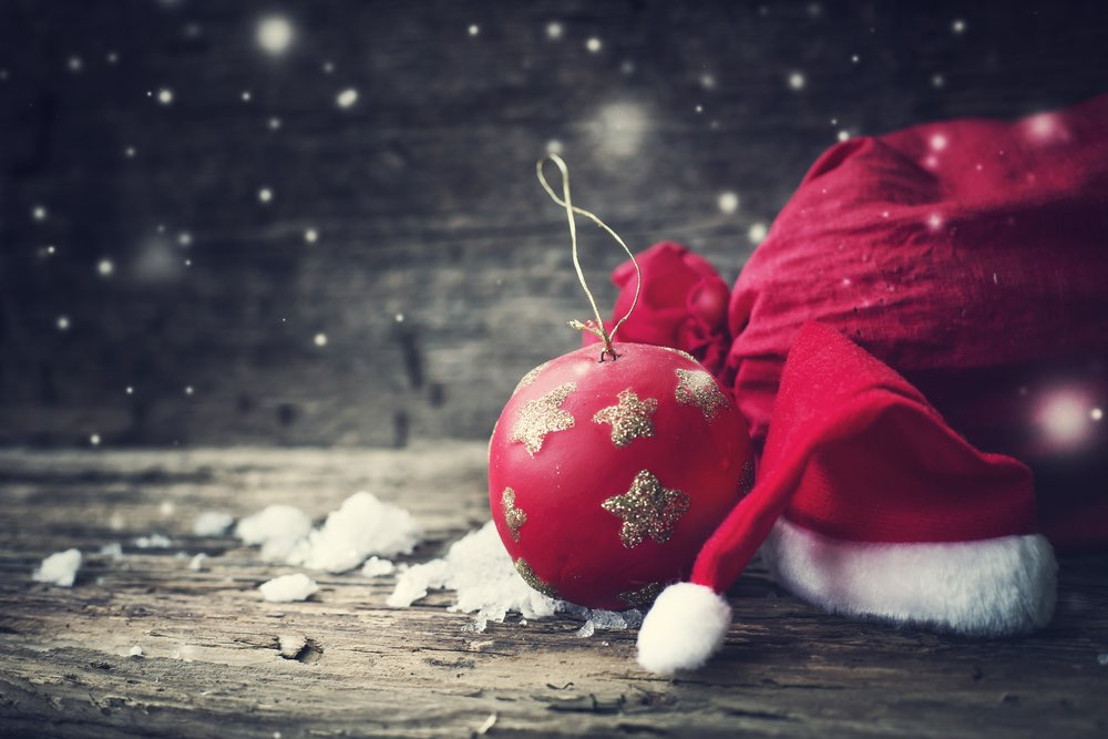 Kerstfoto via Shutterstock.com (http://www.shutterstock.com/pic-318588413/stock-photo-christmas-background-with-christmas-ball-gift-red-hat-and-snow-on-a-wooden-background-christmas.html), iravgustin