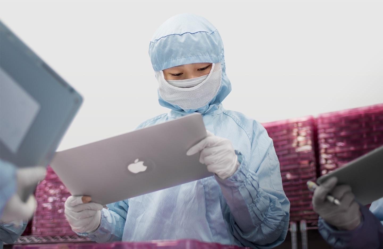 Werknemer werkt in een fabriek aan een scherm voor een MacBook.