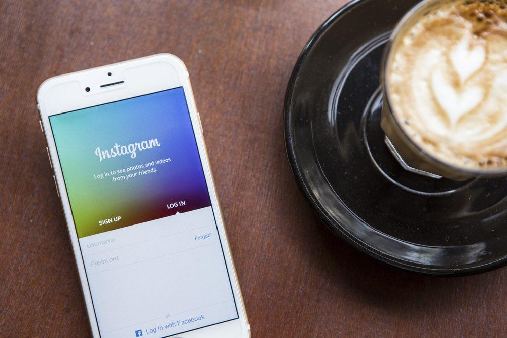 Instagram op iPhone, met kopje koffie, foto via Shutterstock (shutterstock_273074036).
