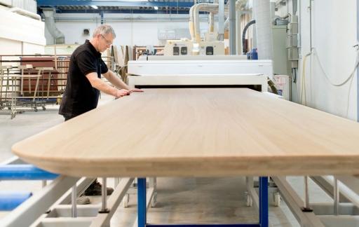 Een medewerker bewerkt de Island Pod-tafel in een CNC-machine