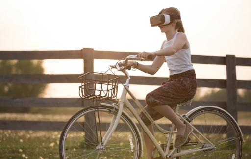 Meisje met VR headset op fiets