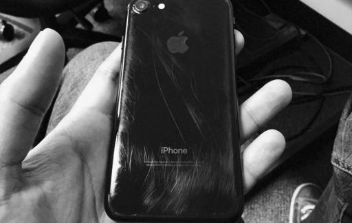 iPhone 7 gitzwart met krasjes op de achterkant.