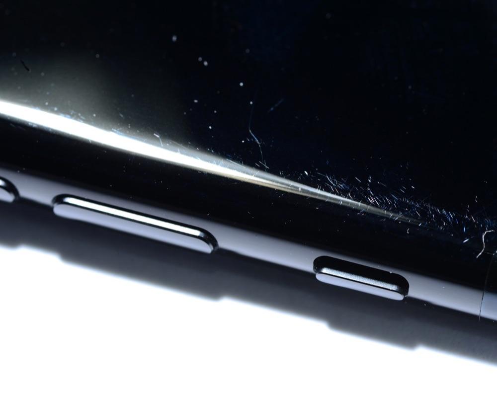 iPhone 7 gitzwart met krasjes op de zijkant.