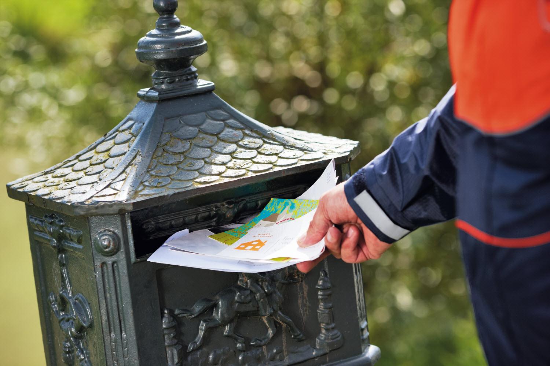 Postbode van PostNL met brievenbus.