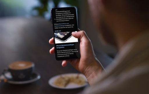 Man leest artikel op iPhone