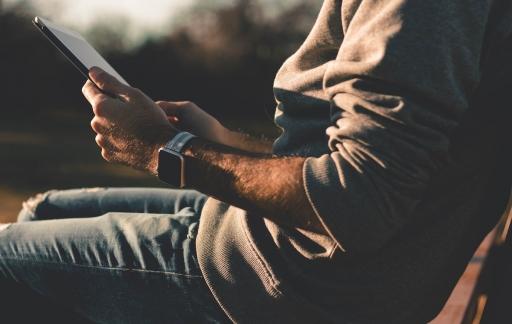 Man met iPad en Apple Watch
