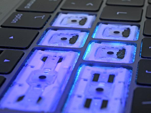 MacBook Pro 2018 toetsenbord teardown van iFixit met stofdeeltjes.