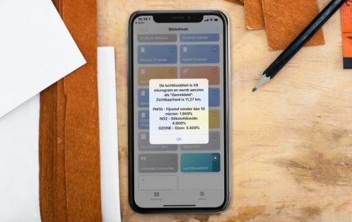 iPhone op bureau met Luchtkwaliteit Siri Shortcut als screenshot.
