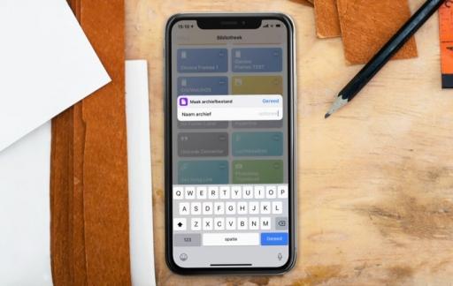 iPhone op bureau met Zip & Share Siri Shortcut als screenshot.
