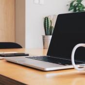 Tips voor thuiswerken: MacBook, iPhone en meer op bureau.