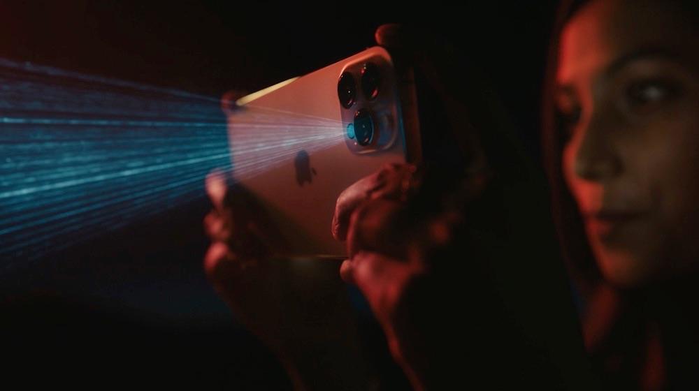 Vrouw houdt iPhone 12 Pro vast met duidelijk zichtbare LiDAR-lichtbundel