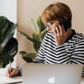 Vrouw met iPhone, bellend met MacBook