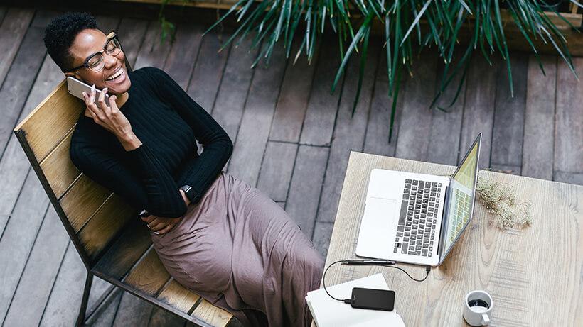 Bellende vrouw met MacBook en Belkin powerbank