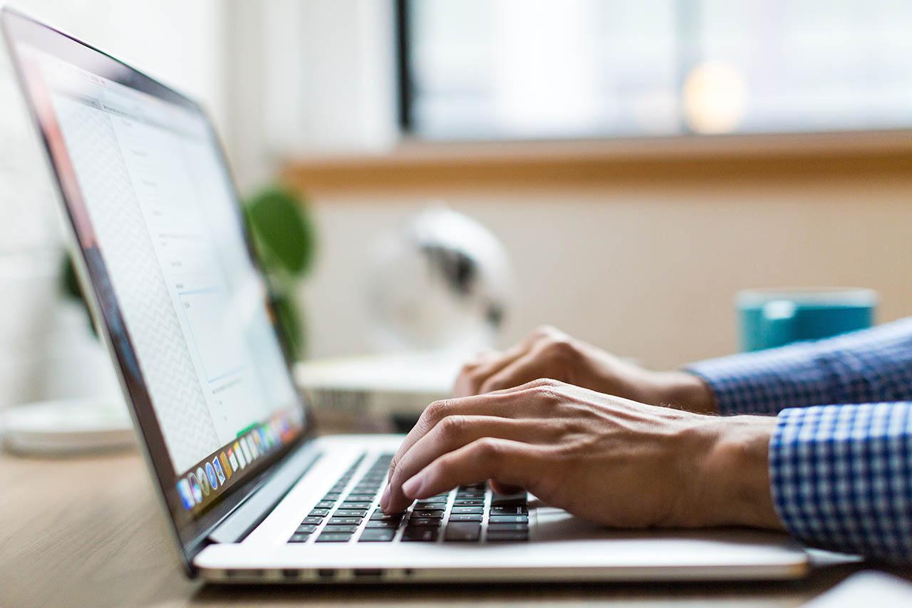 Handen typen op MacBook-toetsenbord