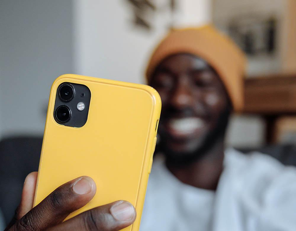 Man met iPhone in geel hoesje