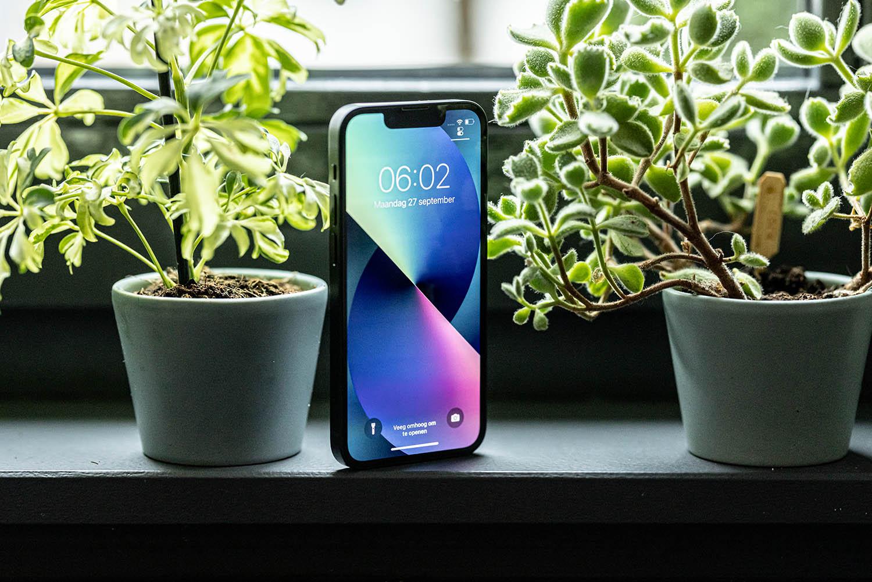 iPhone 13 mini staand tussen planten.